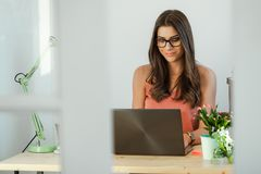 Entrepreneur pretty woman sitting at home desk, working. Royalty Free Stock Image