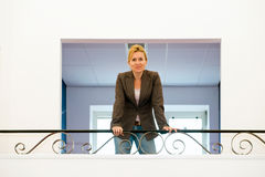 Entrepreneurial woman. Confidently posing entrepreneur, leaning on a balcony in an office building Royalty Free Stock Images