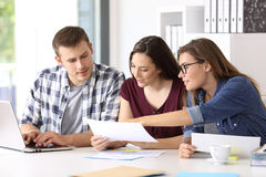 Entrepreneurs analyzing a report at office. Three entrepreneurs analyzing and commenting reports together sitting in a desk at office Stock Image