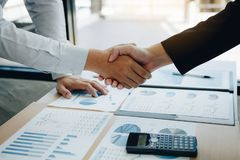 Entrepreneurs collaboration deal shaking hands in a modern office and financial paper graph on desk stock images