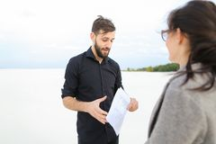 Entrepreneurs male and female discussing project of beach ar. Entrepreneurs create project of beach arrangement, colleagues come to location to discuss Royalty Free Stock Images