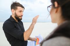 Entrepreneurs male and female discussing project of beach ar. Entrepreneurs create project of beach arrangement, colleagues come to location to discuss Royalty Free Stock Image
