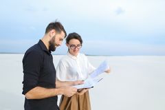 Entrepreneurs male and female discussing project of beach ar. Entrepreneurs create project of beach arrangement, colleagues come to location to discuss Royalty Free Stock Photos