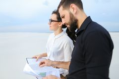 Entrepreneurs male and female discussing project of beach ar. Entrepreneurs create project of beach arrangement, colleagues come to location to discuss Stock Images