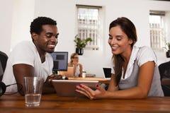Entrepreneurs de démarrage discutant une tablette image libre de droits