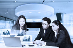 Entrepreneurs looking at financial growth chart. Three multi ethnic entrepreneurs working in the office while looking at financial growth chart on the laptop Royalty Free Stock Photo