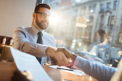 Entrepreneurs making agreement. Confident bearded businessman in eyeglasses sitting at cafe table and shaking hand of his partner and smiling after making Royalty Free Stock Images
