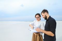 Entrepreneurs male and female discussing project of beach ar. Entrepreneurs create project of beach arrangement, colleagues come to location to discuss Stock Photo
