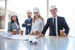 Entrepreneurs multi-ethniques dans le tenue de soirée fonctionnant avec des modèles au secteur de construction Photos stock