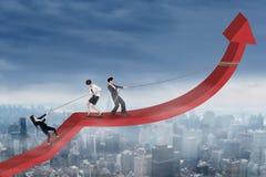 Entrepreneurs pulling a business chart upward Stock Photos