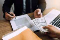 Entrepreneurs are receiving money that is a bribe of their partners with both of whom are corrupt in the company room.  royalty free stock image