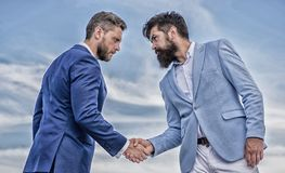 Entrepreneurs shaking hands symbol successful deal. Sure sign you should trust business partner. Men formal suits. Shaking hands blue sky background. Business royalty free stock photography