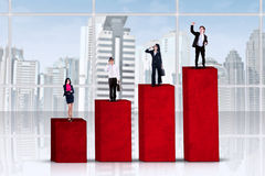 Entrepreneurs standing over business graph Stock Photography