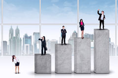 Entrepreneurs standing on the ranking bars. Businesspeople standing on the ranking bars, symbolizing the business growth progress royalty free stock photos