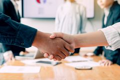 Entrepreneurs team collaborating deal shaking hands in a modern office.  royalty free stock photo