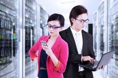 Entrepreneurs travaillant dans la salle de centre de traitement des données Image libre de droits