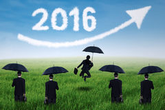 Entrepreneurs with umbrella and numbers 2016 at field. Group of five businesspeople with umbrella on the meadow looking at upward arrow and numbers 2016 Royalty Free Stock Images
