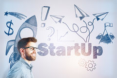 Entrepreneurship concept. Side portrait of cheerful young businessman on light background with rocket sketch. Entrepreneruship concept Stock Image