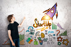 Entrepreneurship concept. Side view of young businessman pointing at concrete wall with rocket sketch. Entrepreneurship concept Royalty Free Stock Photos