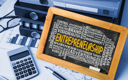 Entrepreneurship with related word cloud handwritten on blackboa Royalty Free Stock Images