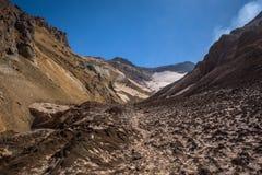 Entrer dans le cratère du volcan de Mutnovsky sur la cendre a couvert la neige éternelle Photo libre de droits