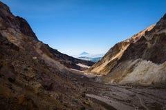 Entrer dans le cratère du volcan de Mutnovsky sur la cendre a couvert la neige éternelle Photo stock