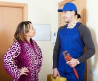 Entretenez le travailleur dans l'uniforme est venu à la femme au foyer Image stock