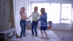 Entretenimiento de la diversión con la madre, las muchachas felices que saltan en cama con la mamá alegre y risa durante resto al almacen de metraje de vídeo