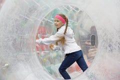 Entretenimiento del ` s de los niños en la diversión parque-que corre dentro del zorb Imágenes de archivo libres de regalías