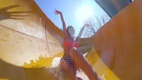 Entretenimiento del verano en el parque del agua, muchacha alegre feliz en el traje de baño que se divierte en aquapark el vacaci almacen de video