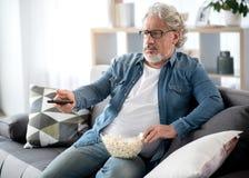 Entretenimiento masculino mayor tranquilo con la televisión Fotografía de archivo
