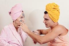 Entretenir affectueux de couples d'amusement la peau Se reposer sur le divan en serviettes et se causent le masque d'argile sur l Photos stock