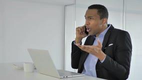 Entretien afro-américain occasionnel fâché de Yelling During Phone d'homme d'affaires, négociant clips vidéos