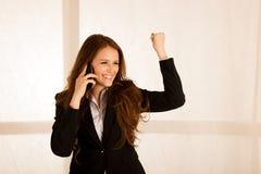 Entretien attrayant de femme d'affaires à un téléphone intelligent à sa GE de bureau Image libre de droits