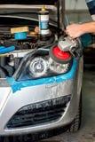 Entretien automobile avec le nettoyage de phare de voiture avec la machine d'amortisseur de puissance Image libre de droits