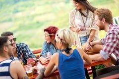 Entretien décontracté de joueurs de carte et amusement de avoir avec la boisson d'alcool Photographie stock