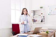 Entretien d'affaires, femme consultant par le téléphone au bureau Photographie stock