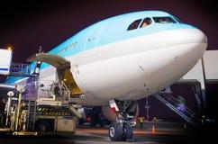 Entretien d'un gros avion dans le parking à l'aéroport la nuit Images stock