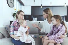 Entretien de babysitter avec la mère des enfants Elle tient le bébé dans des ses bras La mère des enfants gronde l'infirmière Image stock