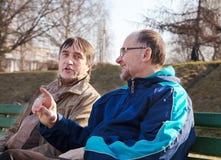 Entretien de deux hommes plus âgés sur un banc de parc Image libre de droits
