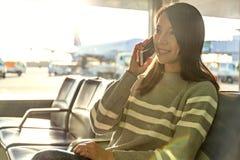 Entretien de femme au téléphone portable à l'aéroport Image stock