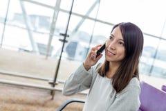 Entretien de femme au téléphone portable dans l'aéroport Photos libres de droits