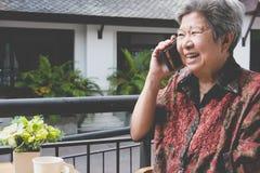 entretien de femme plus âgée au téléphone portable en café speakin femelle plus âgé Photos stock