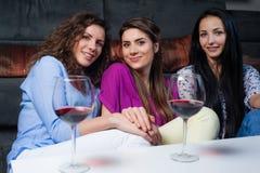 Entretien de fille au-dessus d'un verre de vin Images stock