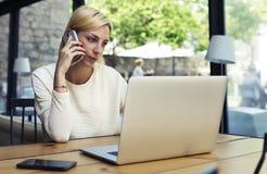 Entretien de personne féminine sur le smartphone tout en regardant l'écran de filet-livre Photo stock
