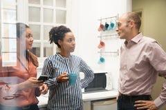 Entretien de trois collègues de travail dans une cuisine de bureau images libres de droits