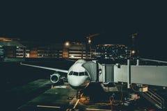 Entretien des avions à l'aéroport de nuit Photographie stock libre de droits