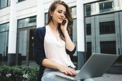 Entretien indépendant de jeune femme par le téléphone portable avec l'information de client et de recherche dans l'Internet photos libres de droits