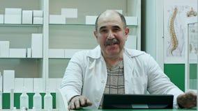 Entretien supérieur de pharmacien à un appareil-photo présentant à conseil de médecine le traitement médical dans la boutique de  banque de vidéos