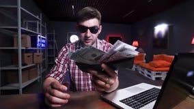 Entretiens d'homme sur la caméra et jets derrière son vieux portefeuille noir arrière complètement d'argent banque de vidéos